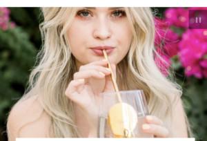 Woman using metal straw to drink beverage
