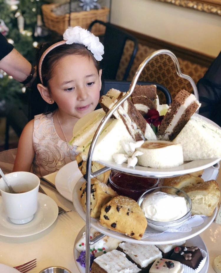 girl looking at tea and sweets on table