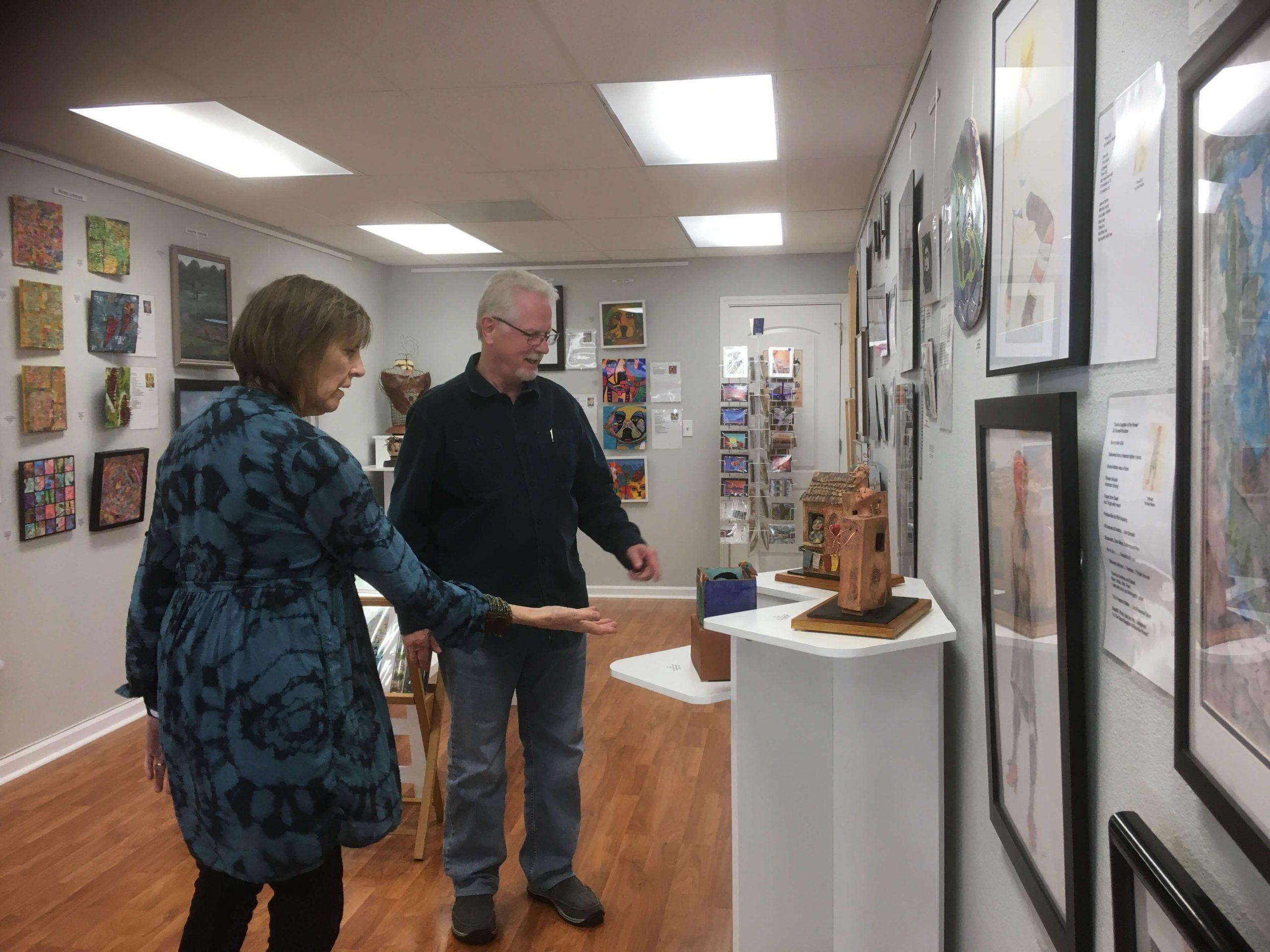 Patrons look at artwork inside HQ Gallery